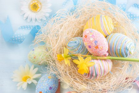 Photo for Easter eggs in the nest with spring flowers over wooden background - Royalty Free Image