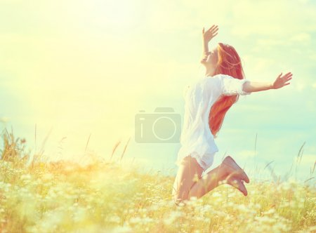 Photo for Beauty model girl in white dress jumping on summer field - Royalty Free Image