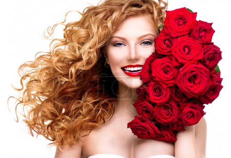 Photo for Beauty woman with long permed red hair and beautiful red roses - Royalty Free Image