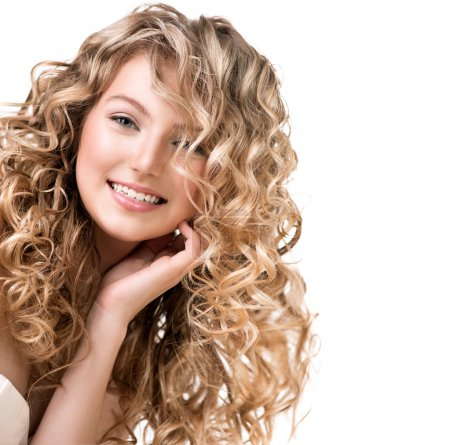 Beauty girl with blonde curly hair. Long permed ha...