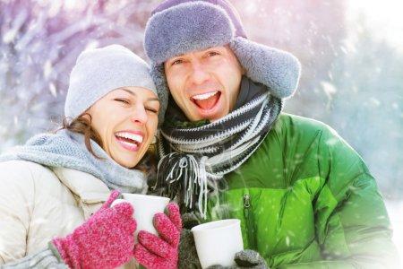 Photo pour Couple heureux hiver s'amuser en plein air. Boissons chaudes - image libre de droit