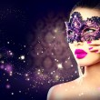 Sexy woman wearing carnival mask over holiday dark...