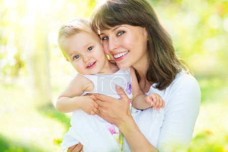 Photo for Beautiful mother and baby playing in a park - Royalty Free Image