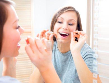 Photo pour Beauté adolescent fille fil dentaire ses dents à la maison. Hygiène dentaire - image libre de droit