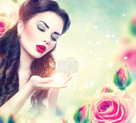 Retro woman  in pink roses garden.