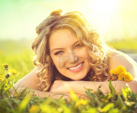 Photo for Beautiful young woman lying on a field, enjoying nature - Royalty Free Image