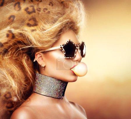 Photo pour Portrait de jeune fille modèle haute couture lunettes de soleil et soufflant des bulles de gomme - image libre de droit