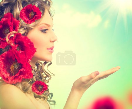 Girl with red poppy flowers in hairstyle