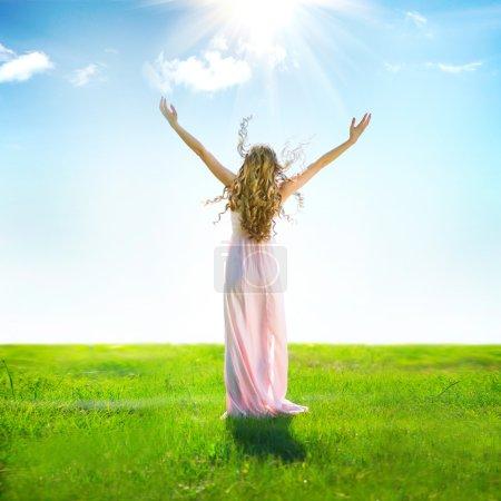Photo pour Vue arrière de la belle femme en plein air levant les mains aux rayons du soleil - image libre de droit