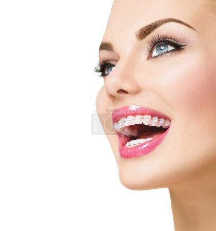 Photo pour Belle femme souriante avec des accolades en céramique sur des dents isolées sur fond blanc - image libre de droit