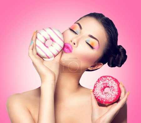 Photo for Beauty fashion model woman holding colorful donuts on pink background - Royalty Free Image