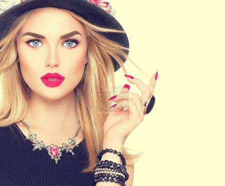 Foto de Hermosa mujer rubia sexy con labios rojos y manicura en sombrero negro moderno - Imagen libre de derechos