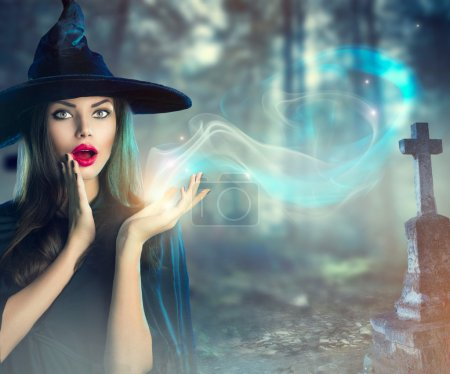 Halloween witch at a dark old spooky cemetery...