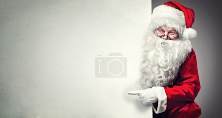 Photo for Smiling Santa Claus pointing on blank advertisement banner background with copy space - Royalty Free Image