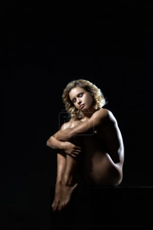 Young, strong athlete girl posing on a dark background