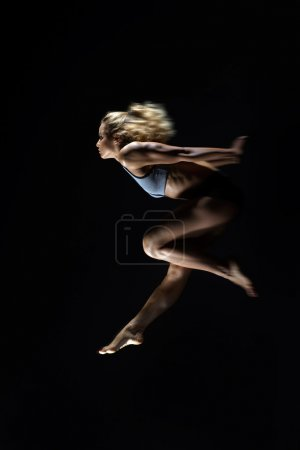 Sport, slim young girl with muscular body  makes a jump