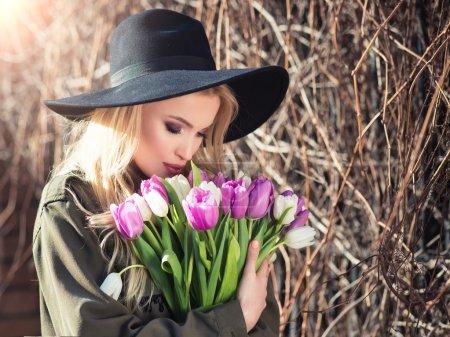 Photo pour Belle fille blonde romantique dans un chapeau noir profite d'un bouquet de tulipes blanches et violettes. Beauté fille à la mode a reçu un bouquet cadeau de fleurs . - image libre de droit