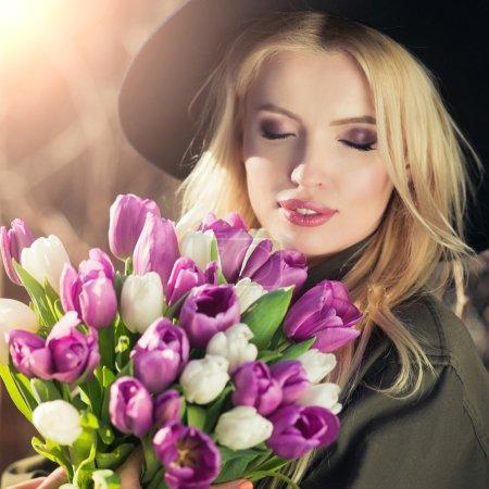 Beautiful blonde girl in a black hat is enjoying tulips bouquet