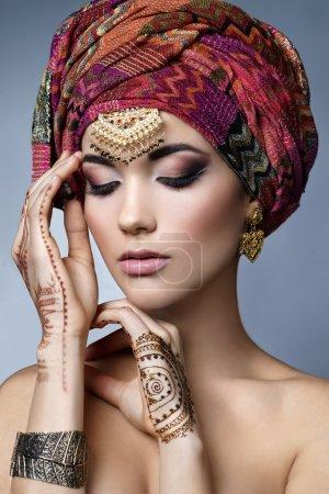 Photo pour Magnifique portrait de femme orientale de mode avec accessoires orientaux- boucles d'oreilles, bracelets et bagues. Fille indienne avec des tatouages au henné et des bijoux de beauté. Modèle hindou avec maquillage parfait. L'Inde. Asie - image libre de droit