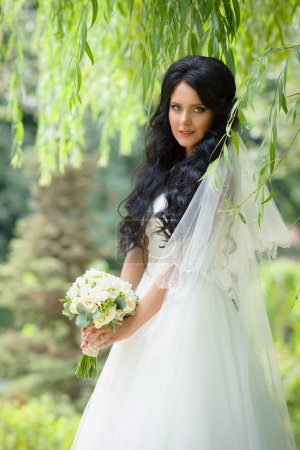 Beautiful brunette bride with a wedding bouquet posing in park