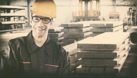 Smiling worker with protective uniform in front of metal proflie