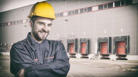 Photo pour Travailleur souriant avec protection uniforme en face de l'expédition des portes de l'entrepôt - image tonique, film rétro filtré dans instagram styl - image libre de droit