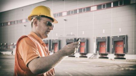 Photo pour Travailleur avec protection uniforme en face de l'expédition des portes de l'entrepôt - image tonique, film rétro filtré dans instagram styl - image libre de droit
