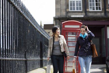 Photo pour Deux femmes blanches et asiatiques heureuses faisant du shopping ensemble, s'amusant et riant . - image libre de droit