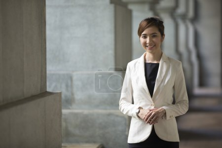 Foto de Mujer de negocios asiática de pie fuera con edificios de oficinas en el fondo. Retrato de una empresaria china mirando a la cámara . - Imagen libre de derechos