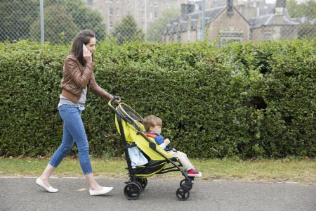 Mum talking on phone  pushing toddler in pram