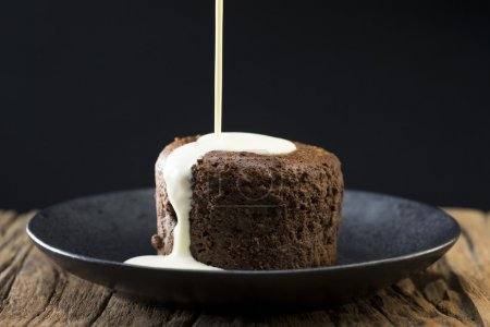 cream being poured over Chocolate Cake