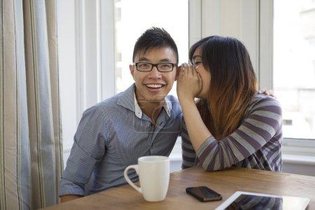 Femme asiatique chuchoter des secrets à une oreille d'amis