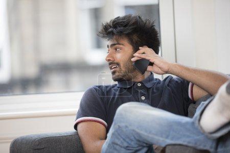 Asian Man using phone at home