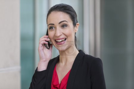 Photo pour Professionnel du Caucase femme d'affaires à l'extérieur dans la ville moderne de parler sur smartphone. - image libre de droit