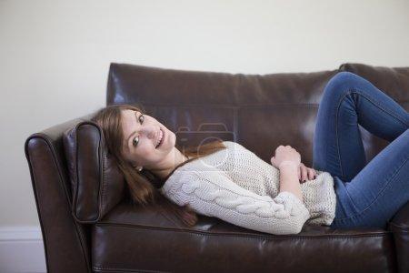Photo pour Portrait d'une jeune femme assise relaxante à la maison sur un canapé . - image libre de droit