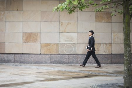 asian businessman walking in city