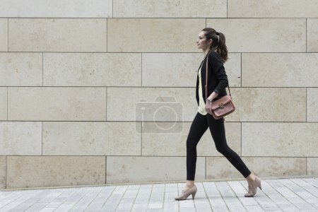 Photo for Side view of a Caucasian Businesswoman walking on city street in front of modern marble wall. - Royalty Free Image
