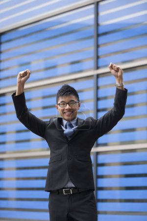 Chinese businessman with his arms raised