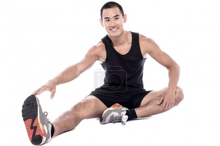 Photo for Young fitness man sitting and making stretching exercises - Royalty Free Image
