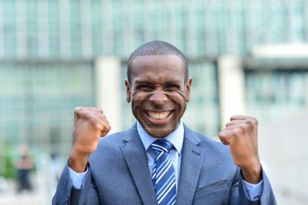 Photo pour Homme d'affaires joyeux montrant son succès avec les bras levés - image libre de droit