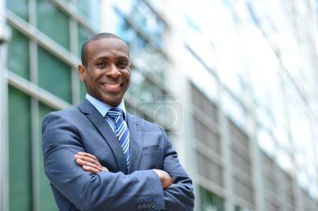 Photo pour Homme d'affaires debout les bras croisés près d'un immeuble de bureaux - image libre de droit