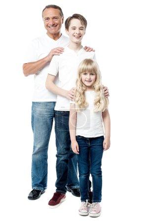 Photo pour Père souriant avec fils et fille posant à la caméra - image libre de droit