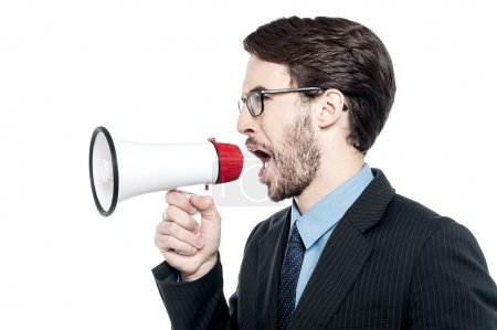 Photo for Angry businessman shouting into a megaphone - Royalty Free Image