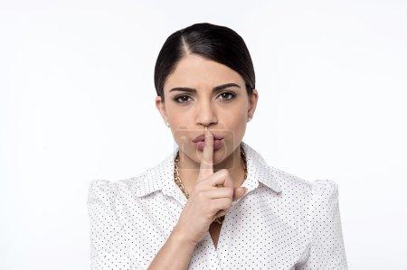 Woman keeping finger on lips