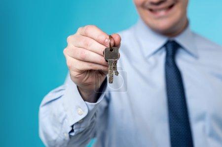 Realtor offering a house key