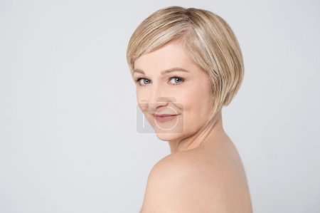 Bare shoulder woman looking at camera