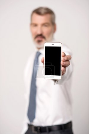 Male executive showing mobile phone