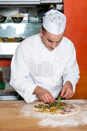 Chef preparing delicious pizza