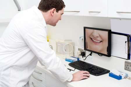 Dentist checking teeth in computer screen