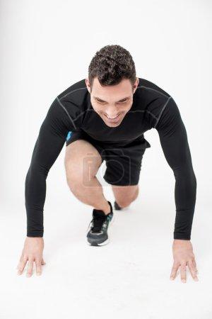 Photo pour Athlète masculin compétitif en position de départ - image libre de droit